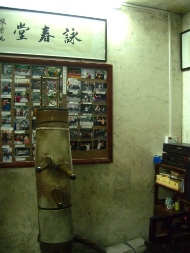Old wooden dummy, with old pictures on the wall